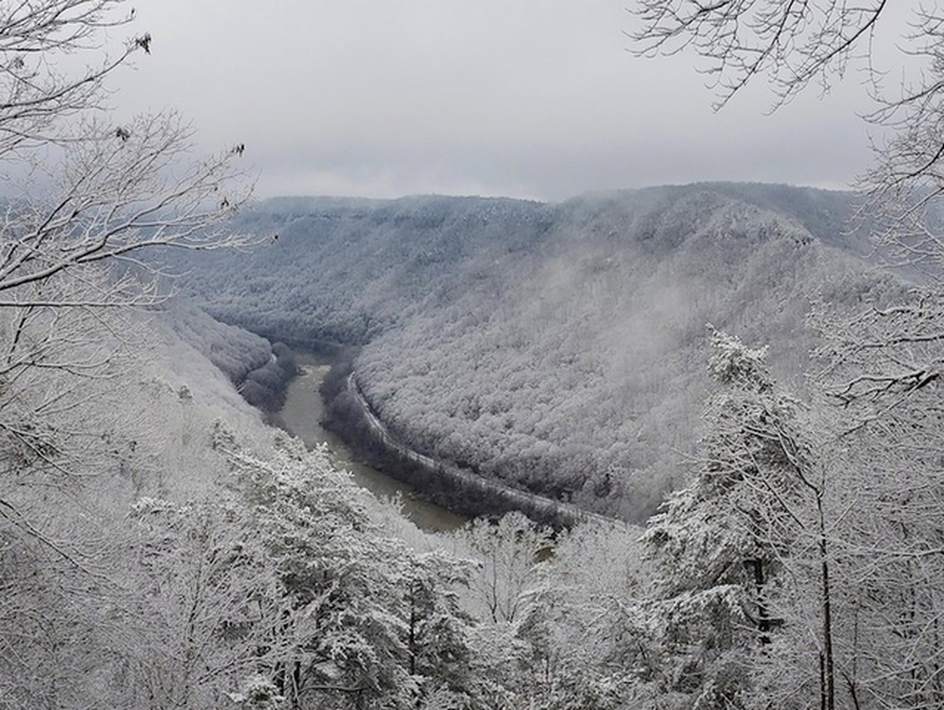 Wide scenic winter view into the New River Gorge also shows rapids below a bend and the road and railroad tracks cut into the wooded slopes on opposite sides of the river